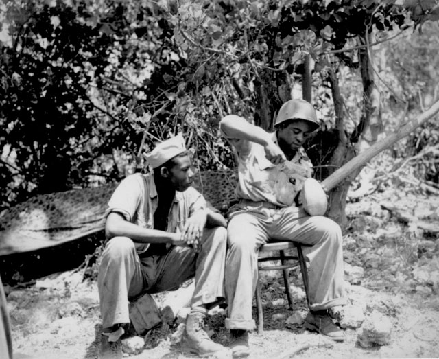 Marine Sgt. F. Smit and Cpl. S. Brown open a coconut to get a cool drink on Saipan. June 1944. 127-GW-1359-85636.