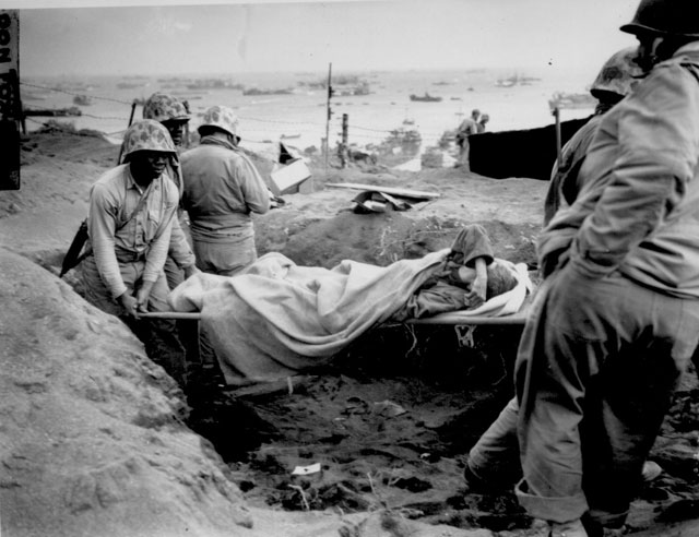Carrying a Jap[anese] prisoner from stockade to be evacuated and treated for malnutrition. Iwo Jima. February 23, 1945. Don Fox. 127-N-110622.