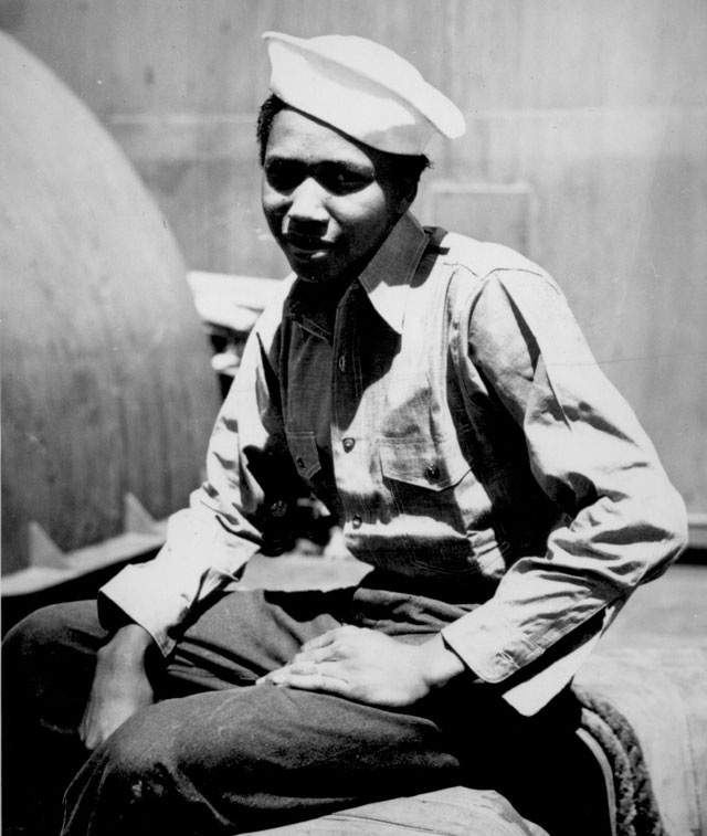 Coast Guardsman Aught Guttery, Jr., first class Steward's Mate, is shown aboard the Coast Guard-manned assault transport on which he served during the initial landings at Guam. N.d. 208-NP-8WWW-9. .