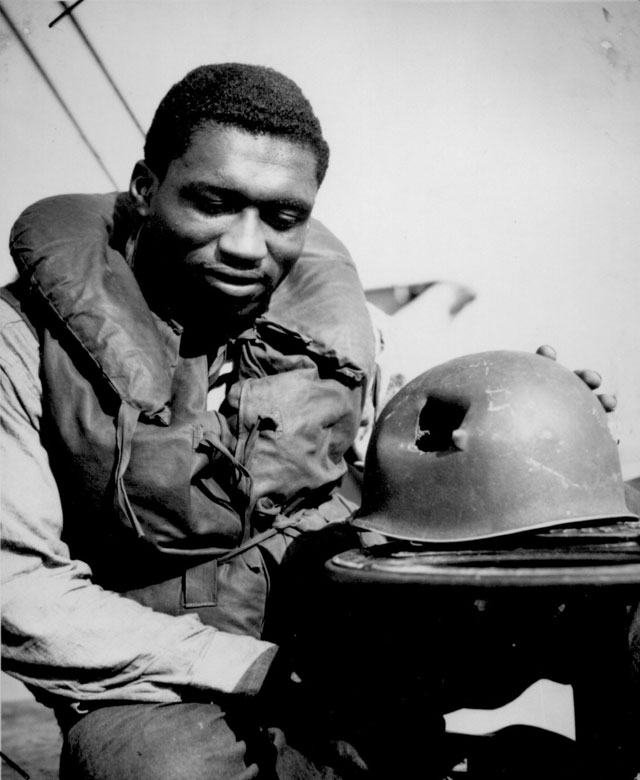 Coast Guardsman Charles Tyner, Fireman first class, examines the jagged shrapnel hole in the helmet he wore during the initial assault on the beaches of Southern France Tyner suffered just a superficial scratch. N.d. 26-G-2748.