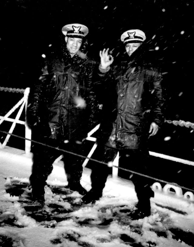 Two Coast Guard officers brave the wintry blasts of snow aboard a Coast Guard cutter on the North Atlantic patrol. The officers who give their cheery greetings despite the icy weather are Lt.(jg.) Clarence Samuels (right) and Ens. J.J. Jenkins (left) N.d. 26-G-3686.