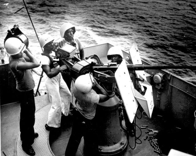Five steward's mates stand at their battle stations, as a gun crew aboard a Coast Guard-manned frigate in the southwest Pacific. On call to general quarters, these Coast Guardsmen man a 20mm AA gun. They are, left to right, James L. Wesley, standing with a clip of shells; L. S. Haywood, firing; William Watson, reporting to bridge by phone from his gun captain's post; William Morton, loading a full clip, assisted by Odis Lane, facing camera across gun barrel. N.d. 26-G-3797.