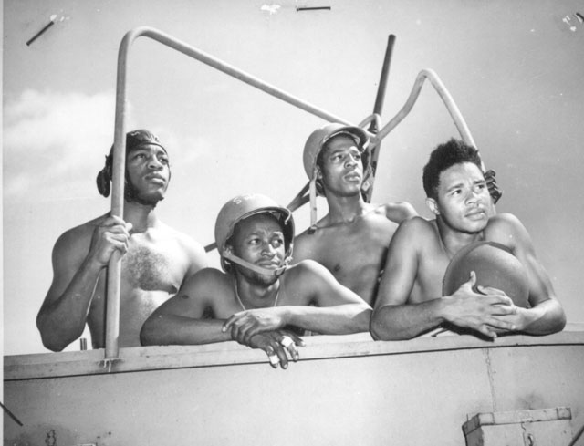 Crew of a 20mm gun aboard a Coast Guard fighting ship are hanging up some new records for speed and accuracy. Left to right: Daniel Moore, Walter L. Bottoms, William Wheeler, and Rudolph C. Grimes, all Steward's Mates, second class. N.d. 26-G-3151.