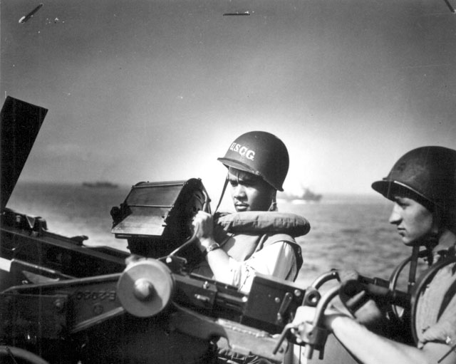 Two Ohio Coast Guardsmen [John R. Smith, on the left, and Daniel J. Kaczorowski] stand at their gun aboard a Coast Guard-manned invasion transport on which they served during the invasion of Normandy. Smith, steward's mate, third class, also served during assaults against North Africa, Sicily, and Italy. N.d. 26-G-2624.