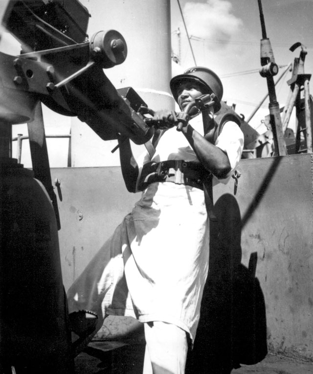 A startling change is affected by Coast Guardsman Dorall Austin, Steward's Mate third class, at the alarm of general quarters aboard his Coast Guard assault transport somewhere in the Pacific. With the enemy sighted Austin springs from his duty in the ship's galley to his battle station as a gunner N.d. 208-NP-8UUU-2.
