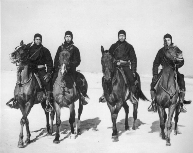 These Negro members of a Coast Guard Horse Patrol unit patrol beaches in the New Jersey area in all kinds of weather. Left to right: Seamen first class C. R. Johnson, Jesse Willis, Joseph Washington, and Frank Garcia. N.d. 208-NP-8CCC-1.