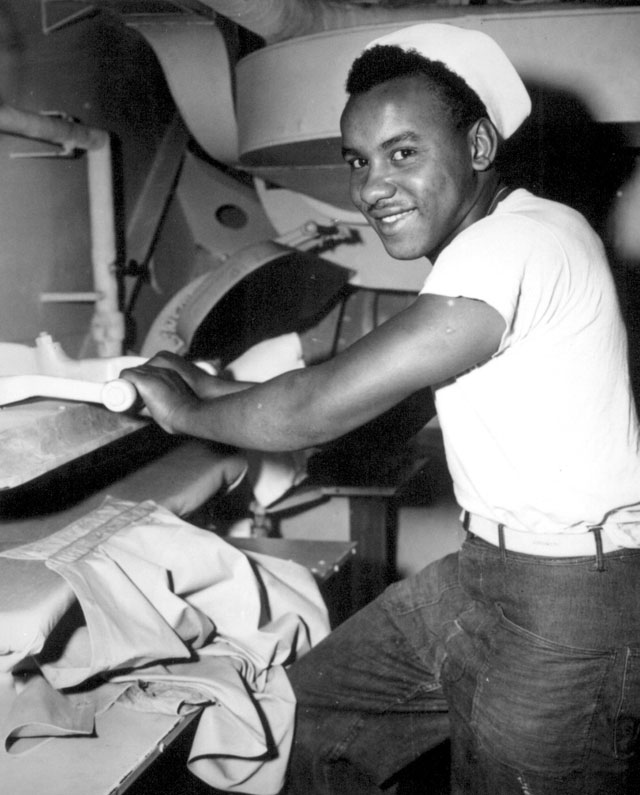 Coast Guardsman Levern Robinson, Seaman first class, is shown at work in the ship's laundry, aboard a Coast Guard manned troop transport operating in the Atlantic. The transport is engaged in bringing home our victorious fighting men from liberated Europe for well-earned leaves and reassignments. N.d. 208-NP-8WWW-10.