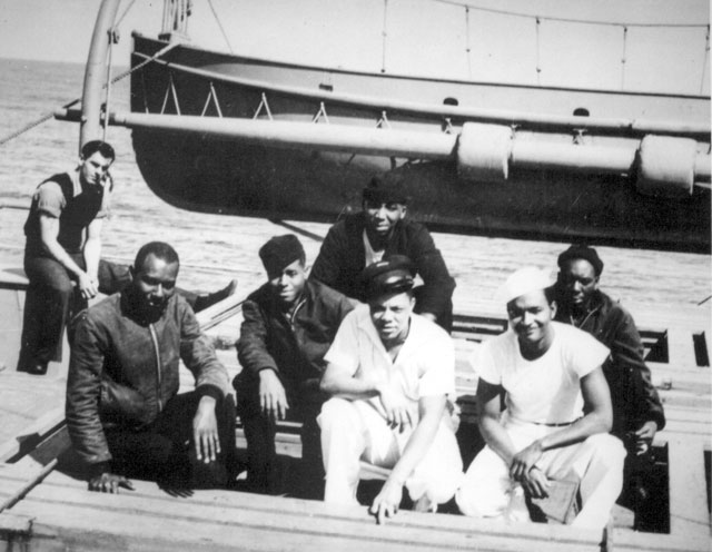 These Coast Guardsmen, crew members of a Coast Guard combat cutter, help patrol sea lanes and protect convoys bound for the European battle zone. Left to right: Atwood Taylor, Steward's Mate first class; Richard U. Mitchell, Steward's Mate first class; R. E. Bird, Jr., Steward's Mate second class;  Robert Woldon, Steward's Mate first class; Grover Taylor, Steward's Mate first class; [and] Jacob A. Lawrence, Steward's Mate second class,  who is also the ship's artist. N.d. 208-NP-8LLL-1.
