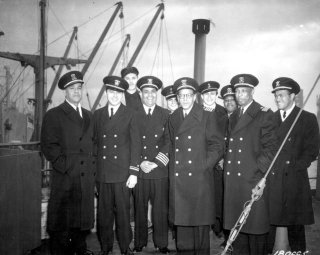 Captain and crew of a new Liberty Ship [SS Booker T. Washington] just after it completed its maiden voyage to England. (L-R) C. Lastic, Second Mate; T. J. Young, Midshipman; E. B. Hlubik, Midshipman; C. Blackman, Radio Operator; T. A. Smith, Chief Engineer; Hugh Mulzac, Captain of the ship; Adolphus Fokes, Chief Mate; Lt. H. Kruley; E. P. Rutland, Second Engineer; and H. E. Larson, Third Engineer. Captain Hugh Mulzac is fourth from the left on the first row.  February 8, 1943. Baum. 111-SC-180665.