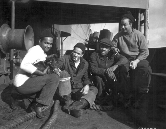 Members of a 'CHECKERBOARD' crew that brought a Liberty Ship from the U.S. to England, fondle their mascot 'BOOKER.' (L-R) R. C. Woods, A. M. Mulzac, W. B. Shepard, and S. O'Neil. February 6, 1943. Baum. 111-SC-180663.