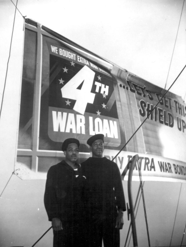 Two U.S. Maritime Service seamen in front of a 4th War Loan poster. N.d. 208-NP-3ZZ-3.