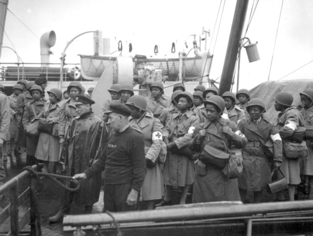 U.S. Army nurses, newly arrived, line the rail of their vessel as it pulls into port of Greenock, Scotland, in European Theater of Operations. They wait to disembark as the gangplank is lowered to the dock. August 15, 1944. Meyer. 111-SC-192605-S.