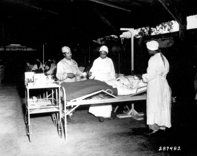 Surgical ward treatment at the 268th Station Hospital, Base A, Milne Bay, New Guinea. Left to right: Sgt. Lawrence McKreever, patient; 2nd Lt. Prudence Burns, ward nurse; 2nd Lt. Elcena Townscent, chief surgical nurse; and an unidentified nurse. June 22, 1944. Pfc. Michael Pitcairn. 111-SC-287482.