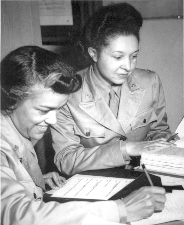 WAACs at work in Temp. Bldg. 'M', 26th Street, Washington, DC, WAAC Headquarters. Left to right: Lts. Harriet West and Irma Cayton, going over their recruiting schedule report. 1942.Wilfred Morgan. 111-SC-144958.