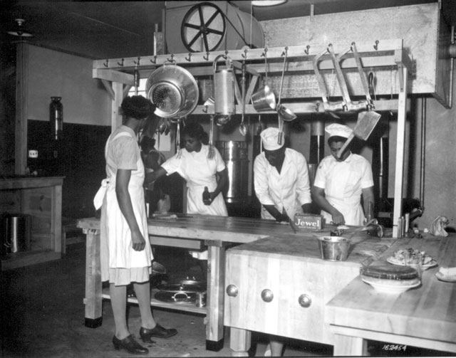 WAAC cooks prepare dinner for the first time in new kitchen at Fort Huachuca, Arizona. December 5, 1942. Oster. 111-SC-162454.
