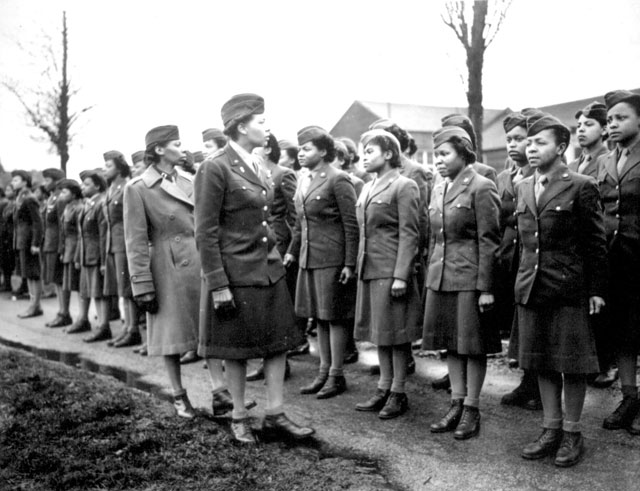 Somewhere in England, Maj. Charity E. Adams, and Capt. Abbie N. Campbell, inspect the first contingent of  Negro members of the Women's Army Corps assigned to overseas service.  6888th Central Postal Directory Bn. February 15, 1945.  Holt. 111-SC-200791.