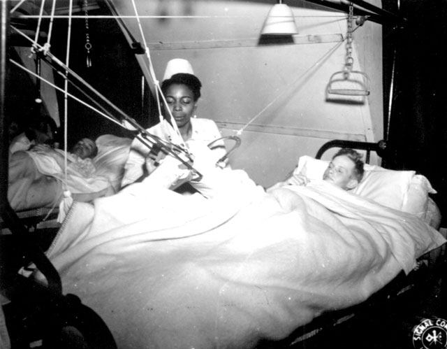 Lt. Florie E. Gant tends a patient at a prisoner-of war hospital somewhere in England. October 7, 1944. 112-SGA-Nurses-44-1676.