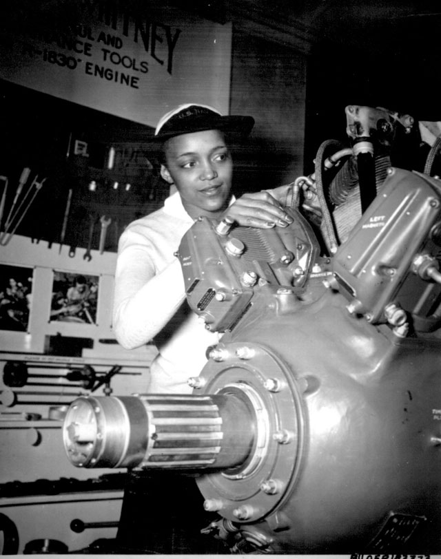 Inspecting a Grumman Wildcat engine on display at the U.S. Naval Training School (WR) Bronx, NY, where she  is a 'boot' is WAVE Apprentice Seaman Frances Bates. 1945. 80-G-183373.