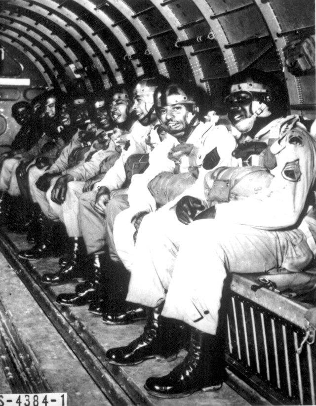 Sixteen Negro soldiers recently won the coveted 'wings' of the U.S. Army paratroopers at Fort Benning, in the southern U.S. state of Georgia. The picture shows some of them riding high in a C-47 transport plane preparing to make one of the required five qualifying jumps. March 1944. 208-FS-1783-1.