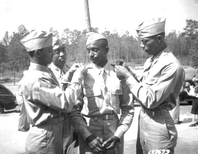 Just after stepping out of Ft. Benning [GA] Theater No. 4 at the conclusion of the 16th O.C.S. graduating exercises, 2nd Lts. Henry C. Harris, Jr.; Frank Frederick Doughton; Elmer B. Kountze; and Rogers H. Beardon (behind) start pinning their brass bars on each others shoulders. May 29, 1942. Golz. 111-SC-137679.