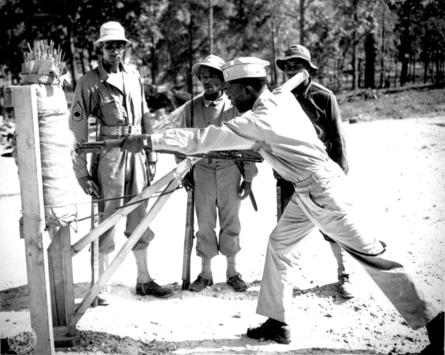 Lt. B. Holmes instructing cadres in the art of parry and long thrust in bayonet practice. Left to right: T/Sgt. Leroy Smith, Pvt. George W. Jones, and Sgt. Leo Shorty, look on. 92d Division, Fort McClellan, AL. November 1942. 111-SC-147979.