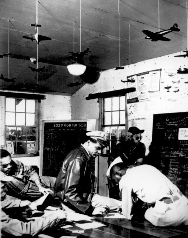 Pilots at Selfridge Field [MI] learn to carry out bombing missions as they would carry them out under actual combat conditions. These pilots are being briefed for a practice raid. Ca. 1943. 208-VM-1-5-68A.