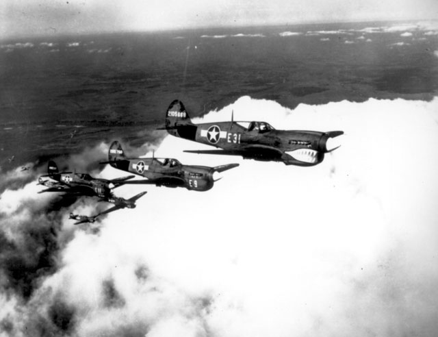 Negro pilots in one of the flight formations which will soon carry them over enemy territory. Here they are flying the shark-nosed P-40 fighter aircraft. Selfridge Field, MI. Ca. 1943. 208-VM-1-5-69G.