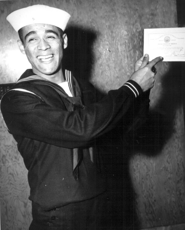 George C. Fields, 32, points proudly to the honor certificate presented him yesterday at graduation exercises for the tenth Negro class to be graduated from the Navy's Service Schools at the U.S. Naval Training Station, Great Lakes, IL. Fields served as President Roosevelt's valet for four years before entering the Navy. Ca. 1943. 208-NP-7QQ-2.