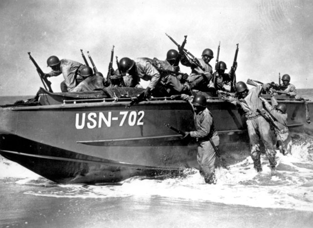 As a landing barge noses onto the beach, members of the Negro Seabee Battalion clamber ashore. This assault training is supplemental to the Seabees' chief work as construction crews for the U.S. Navy. Ca. December 1942. 208-N-570.