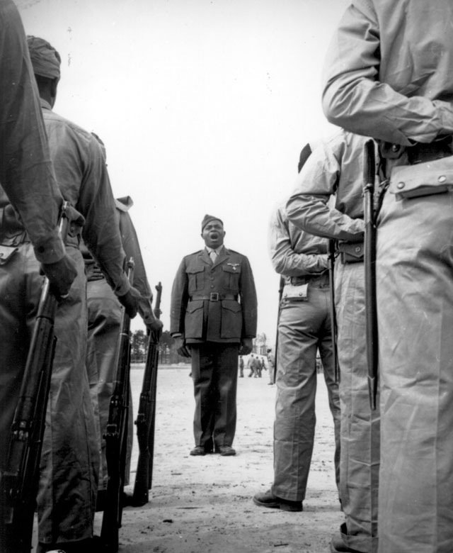 A platoon of Negro `boot recruits' listen to their drill instructor [Sgt. Gilbert Hubert Johnson] whose job is to turn them into finished Marines. Montford Point Camp, NC. Ca. April 1943. 208-NP-10FF-1.
