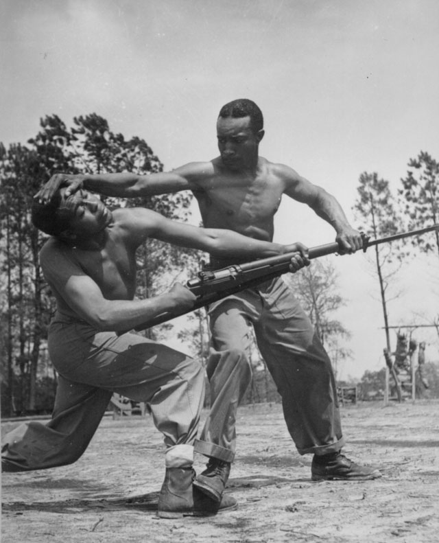 Judo instruction is one of the high spots in the life of the latest addition to the Leatherneck Marines here. An instructor shows a recruit how to make the enemy's bayonet useless. Cpl. Arvin Lou Ghazlo, USMC, giving judo instructions to Pvt. Ernest C. Jones, USMCR. Montford Point Camp, NC. April 1943.  127-N-5334.