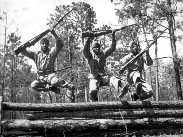 A trio of recruits in training to take their places as fighting Leathernecks in the U.S. Marine Corps, run the rugged obstacle course at Camp Lejeune, NC [Montford Point Camp]. The Marine recruits have shown such excellent results in their aptitudes and leadership capacities that an expanded Navy recruiting program is now underway. April 1943. Pat Terry. 127-N-5335.