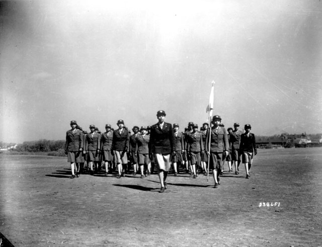 WAAC Capt. Charity Adams of Columbia, NC, who was commissioned from the first officer candidate class, and the first of her group to receive a commission, drills her company on the drill ground at the first WAAC Training Center, Fort Des Moines, Iowa. May 1943. 111-SC-238651.