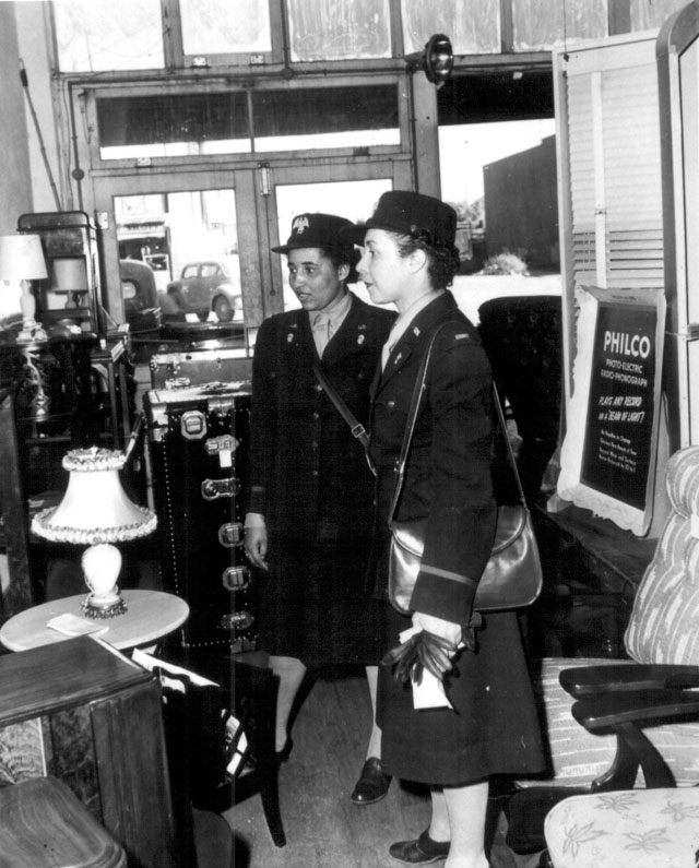 WAAC officers go shopping soon after their arrival at Fort Huachuca, Arizona, these two officers [3d Officers Vera Harrison and Irma J. Cayton] started shopping for lamps and other accessories needed in their recreation hall. 1942. Oster. 111-SC-16248.