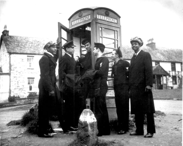 U.S. Coast Guardsmen make use of a telephone booth in Scotland. They are on liberty from their ship, a Coast Guard combat cutter engaged in convoy escort duty. From left to right: Officers' Cook Second Class Joseph Andy, Officers' Steward First Class Casiano Aquino, Gunner's Mate Second Class Vincent G. Igoe,  Electrician's Mate Second Class George Trigony, Radioman Third Class Carlton Lee, and Officers' Steward Second Class Daniel Riley. N.d. 26-G-1550.