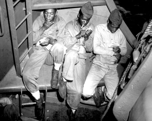 Relaxing aboard a U.S. Coast Guard-manned transport headed for Pacific invasion areas, three Negro Marines catch a smoke. Tomorrow, it will be the smoke of battle. N.d. 26-G-321.