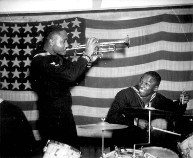 Somewhere in England one of the hottest bands in the European Theater of Operations belongs to a Special United States Naval Construction Battalion. The band leader and trumpeter is Coxswain Thomas J. Lindsey (left), and the drummer is S1c. Edward A. Grant. December 14, 1944. 208-NP-8T-2.