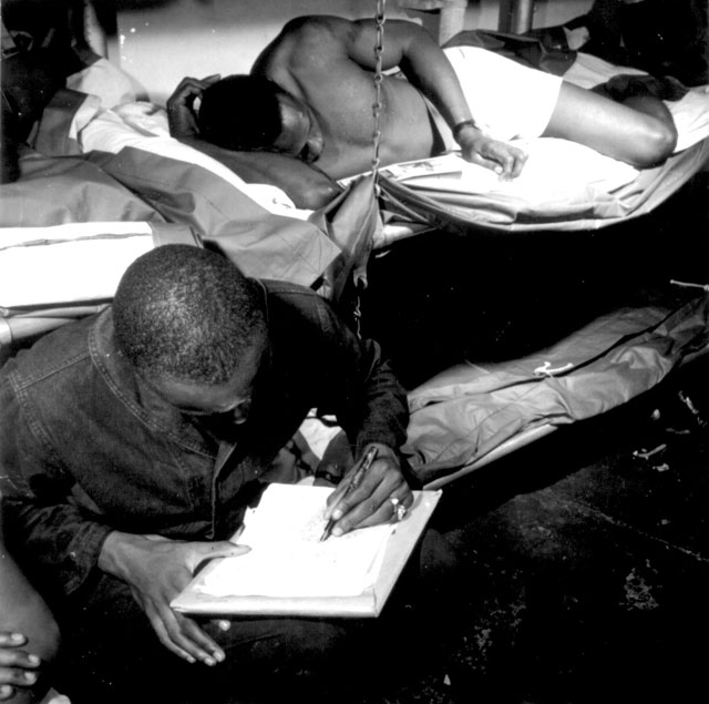 Sailors in their bunkroom aboard the U.S.S. Ticonderoga (CV-14) on eve of the Battle of Manila, PI. Thomas L. Crenshaw (STM1/c) looks at a picture of his three children, while a bunkmate writes a letter home. November 4, 1944. Lt. Wayne Miller. 80-G-46951.
