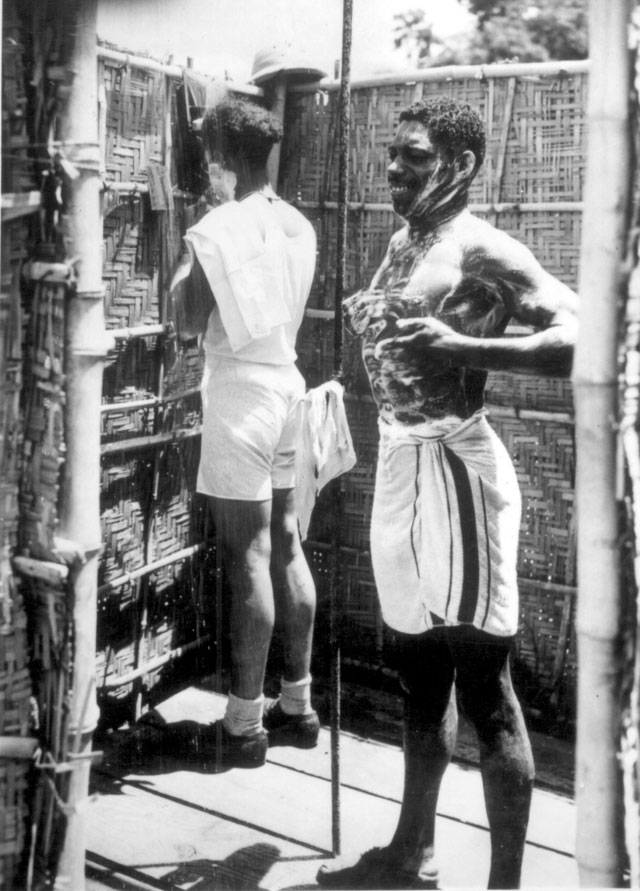 After a hard day's work a shower and shave are in order. Sgt. Wm. H. Whaley soaps himself before taking a cold shower while Sgt. Delos Oliver lathers up. Ca. July 1943. 208-AA-45BB-1.