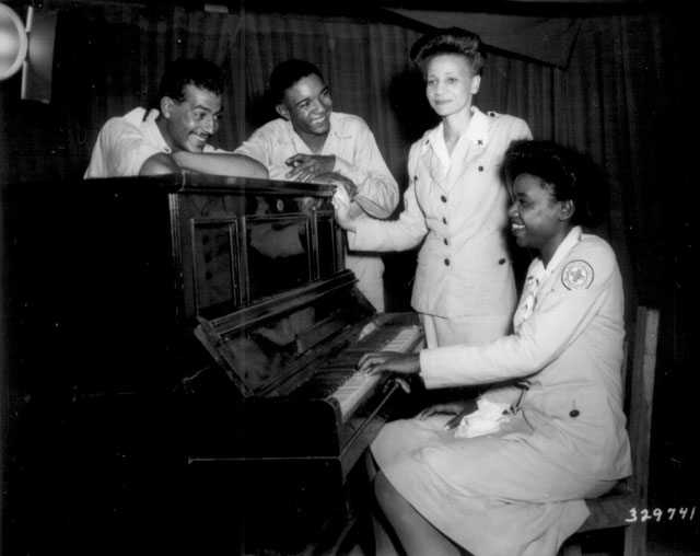 Negro GIs and American Red Cross workers, college graduates, join in some musical fun at Assam, India. Left to right: Cpl. Robert Barttow, Pvt. James Montgomery, Jeannette C. Dorsey, and Willie Lee Johnson. August 23, 1944. Grigg. 111-SC-329741.