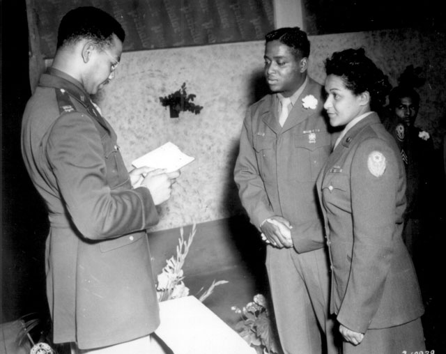 Chaplain William T. Green reads the benediction at the marriage ceremony of Pfc. Florence A. Collins, a WAC of the 6888th Postal Directory Battalion, to Cpl. William A. Johnson of the 1696th Labor Supervision Co. This is the first Negro marriage to be performed in the European Theater of Operations. Rouen, France. August 19, 1945. T/5 L. Kaufman. 111-SC-210939.