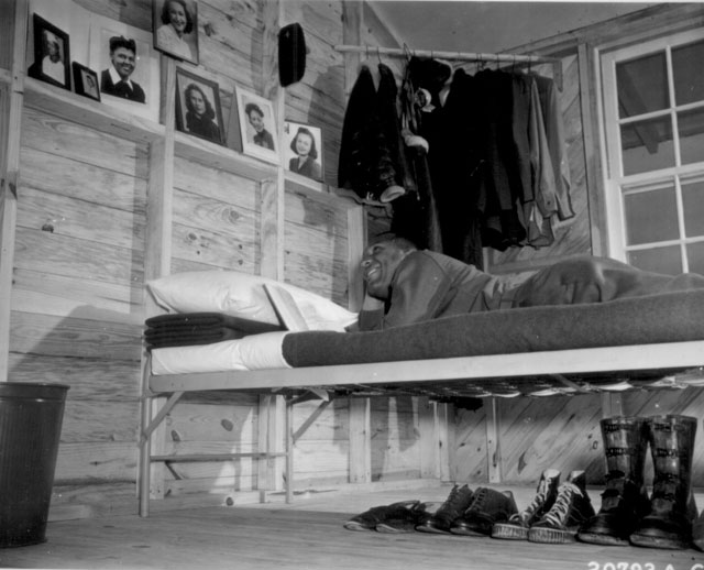 Negro [air cadet] shown on a cot in his barracks studying as he gazes fondly at his collection of photos of his girl friends. N.d. 208-NP-5QQ-9.