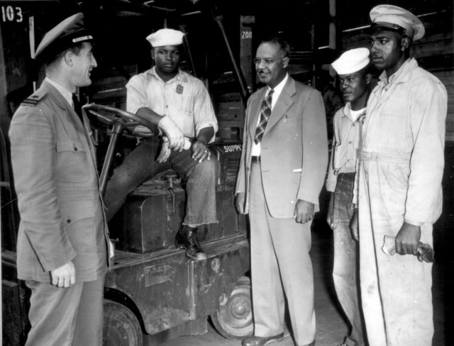 Lester Granger, while inspecting facilities for Negro personnel at NAS, San Diego, CA, stops to chat with Rofes Herring, S1/c; Walter Calvert, S2/c; and Nollie H. Million, civilian employe[e], as Lt. Roper (left) stands by. June 20, 1945. 80-G-33398.