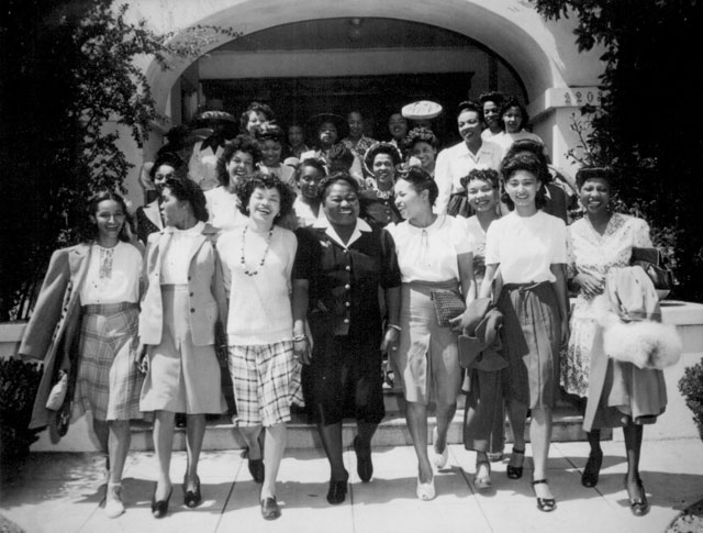 Hattie McDaniel (center), Chairman of the Negro Division of the Hollywood Victory Committee, takes time off from rehearsals to lead a caravan of entertainers and hostesses to Minter Field, for a vaudeville performance and dance for soldiers stationed there. The young lady to the right of Miss McDaniel is Miss Virginia Paris, noted concert singer. N.d. 208-NS-4264-5.