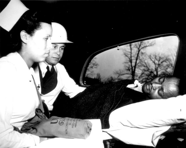 After receiving first aid treatment in practice raid in Washington, DC, air-raid 'victim' is removed to hospital by a Medical Corps of the Office of Civilian Defense. The physician is Dr. Charles Drew. N.d. Roger Smith. 208-NP-4W-2.