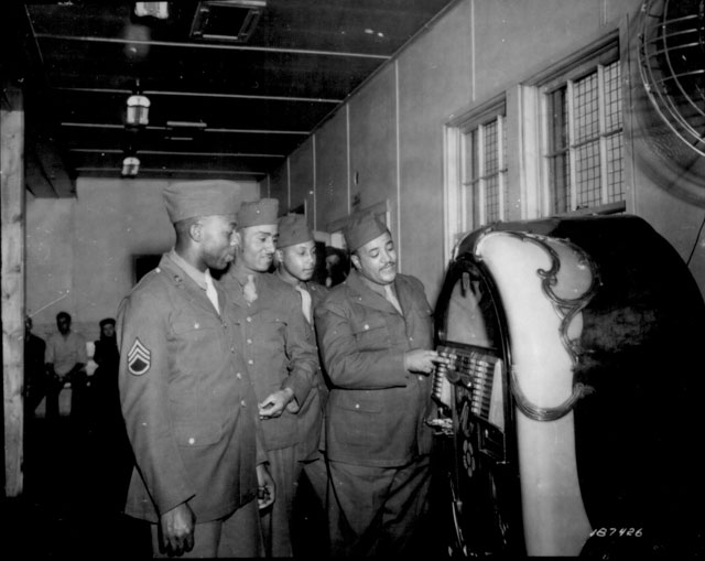 First of the famous Mills Brothers quartet to enter Army service, Pvt. Harry Mills stops at the jukebox in the Reception Center PX to hear how he sounds on one of the latest Mills Brothers recordings. Left to right: S/Sgt. Arthur Whyte, Sgt. Robert Seymour, Pfc. George Blair, and Pvt. Harry Mills. Fort Custer, MI. 1943 111-SC-187426.
