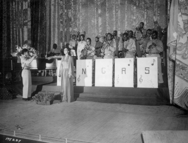 Miss Josephine Baker, popular stage performer, sings the National Anthem as the finale to the show held in the Municipal Theater, Oran, Algeria, N. Africa. The band is directed by T/Sgt. Frank W. Weiss.  May 17, 1943. 111-SC-175237.