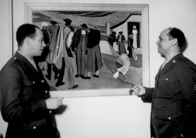 Sgt. Romare Bearden, noted young Negro artist whose paintings have been exhibited in galleries and museums  in several metropolitan centers is shown (right) discussing one of his paintings,  'Cotton Workers,' with Pvt. Charles H. Alston, his first art teacher and cousin. Both Bearden and Alston are  members of the 372nd Infantry Regiment stationed in New York City.  Ca. February 1944. Roger Smith. 208-NP-6W-1.
