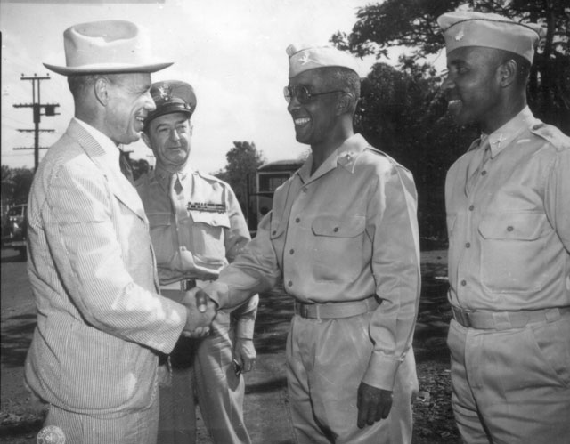 After inspecting a regiment of Negro artillerymen during a visit to Hawaii, Under Secretary of War Robert P.  Patterson congratulates Col. Chauncey M. Hooper, commander of the unit,  while Lt. Gen. Robert C. Richardson, Jr. and Col. Harry B. Reubel, watch with approval.  August 1943. 107-T-7-2.