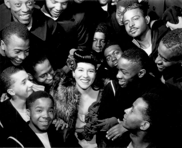 Surrounded by recruits, Marva Louis, wife of champion Joe [Louis], takes time out from a tour of nightclubs to  entertain men in the Negro regiments at the U.S. Naval Training Station, Great Lakes, IL.  Some 2,000 bluejackets gathered in a regimental drill hall to hear her songs.  N.d. 208-NP-8J-2.